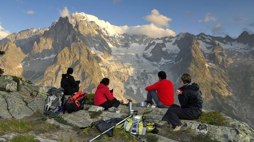 Four hikers eating while looking at a mountain view