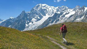 Single hiker walking on trail with mountains in background