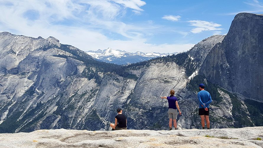 hikers standing atop stony mountain looking at view