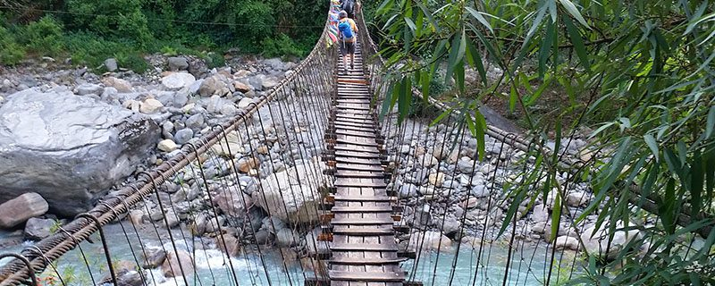wooden suspension bridge over rocks and river