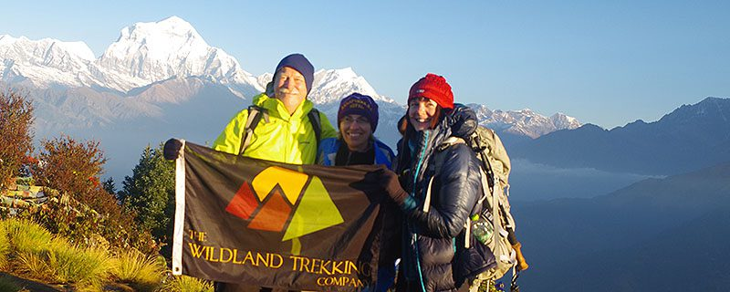 Three hikers hold Wildland Trekking flag on mountain