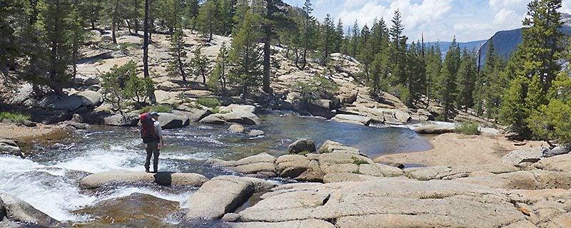 hiker on stony shoreline beside California river
