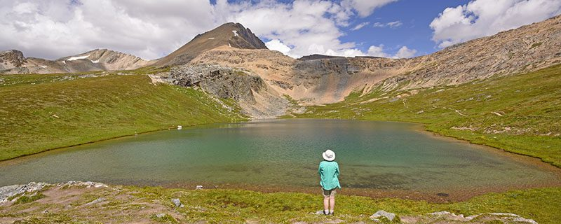Hiker standing at water's edge with mountain in distance