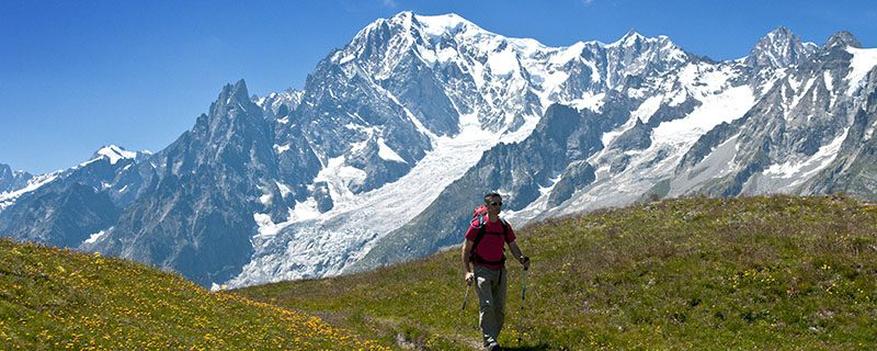 Hiker on trail with mountain behind him