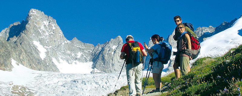 Hikers admiring large glacier from trail