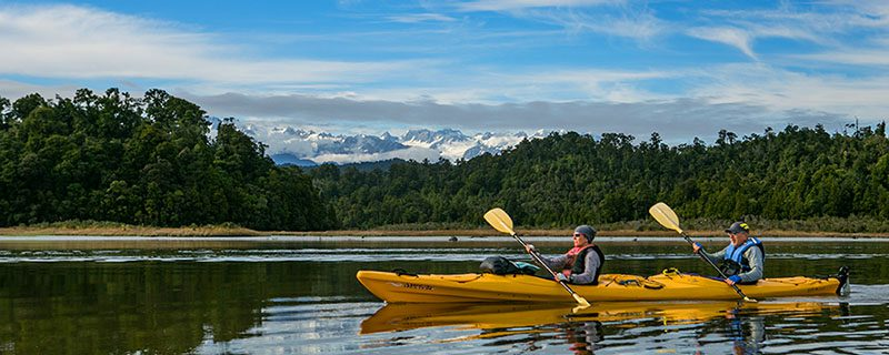 Kayakers on water with mountains