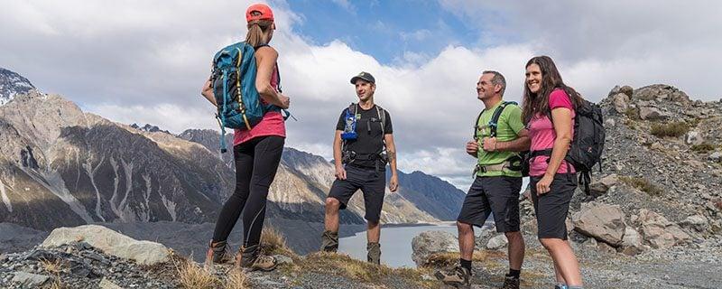 Hikers talking on rocky mountain