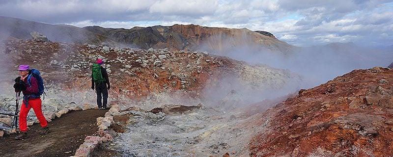 Hikers near red Icelandic hot springs