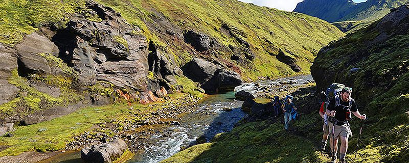 Hikers near river passing through grassy ravine