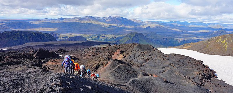 Hikers climbing rocky hill in Iceland