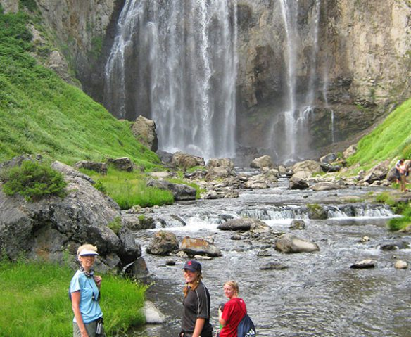 hikers by waterfall at yellowstone