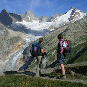 Two hikers before large glacier