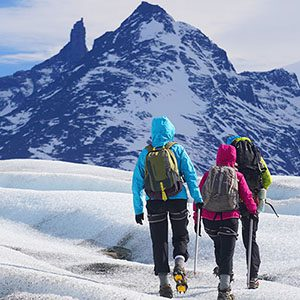 Three hikers walking toward snowy Patagonian mountain