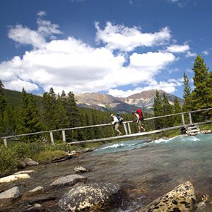 hikers crossing a river on suspension bridge