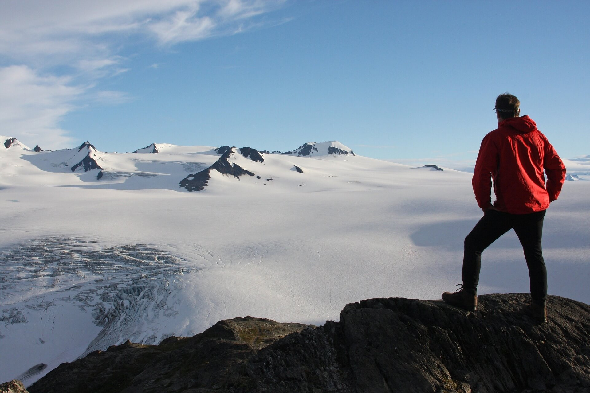 A hiker looking out at the Exit Glacier in Fjords National Park, Alaska