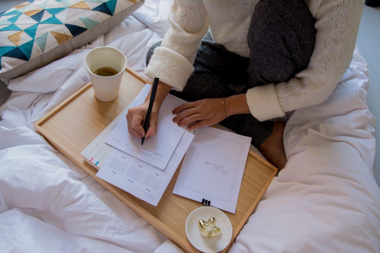 women on bed planning her training schedule