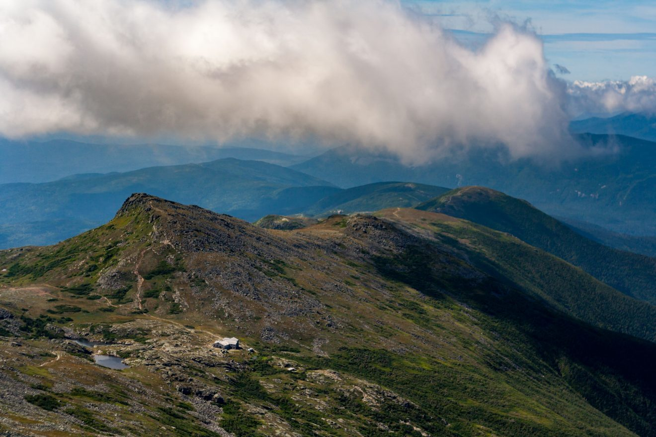 A vista of the White Mountains of New Hampshire from the summit of Mount Washington, the hut at Lake of the Clouds on the ridge.