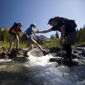 guides helping woman cross river in Canadian Rockies